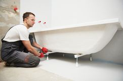 Bathtube installation. plumber installing and mounting bath. Plumber installing and mounting bathtube. home renovation of bath sanitary. levelling with laser royalty free stock photo