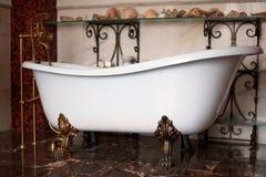 Bathtube libre del clawfoot de bronce de lujo del vintage en interior exquisito Fondo caliente oscuro del color con las cáscaras fotografía de archivo libre de regalías