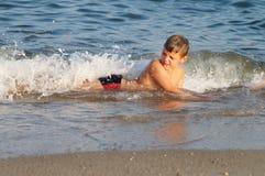 Batida da criança por uma onda do mar foto de stock