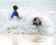 Batida da menina e do irmão pequeno pela onda grande Fotos de Stock