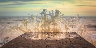 Batida da plataforma por uma onda no por do sol Imagens de Stock Royalty Free