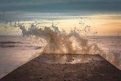 Batida da plataforma por uma onda no por do sol Imagem de Stock Royalty Free
