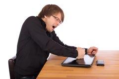 Batida irritada do homem com seu punho em seu portátil Fotografia de Stock