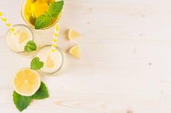 Batido amarelo do limão nos frascos de vidro com palha, folha da hortelã, mel, vista superior Imagens de Stock