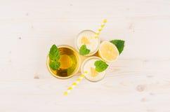 Batido amarelo do limão nos frascos de vidro com palha, folha da hortelã, mel, vista superior Fundo branco da placa de madeira, e Fotos de Stock