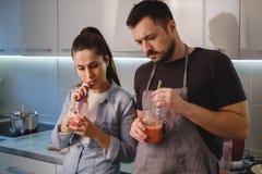 Batido bebendo dos pares tristes na cozinha fotos de stock royalty free