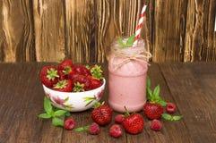 Batido cor-de-rosa da morango e da framboesa em um vidro do frasco de pedreiro com palha e as bagas dispersadas Imagens de Stock Royalty Free