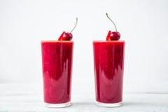 Batido da cereja e bagas saborosos no fundo branco Milk shake natural fresco imagens de stock royalty free