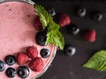 Batido da framboesa e do mirtilo com agitação de leite da dieta do superfood do cocktail da baga da opinião superior da hortelã fotos de stock