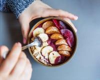 Batido de Acai, granola, sementes, frutos frescos em uma bacia de madeira nas mãos fêmeas na tabela cinzenta Comendo a bacia saud fotos de stock