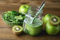 Batido de fruta verde recentemente misturado no frasco de vidro com palha Verde Apple Kiwi Detox Healthy Food Toned de Aragula do foto de stock