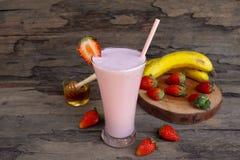 Batido de leche colorido rojo del zumo de fruta de los smoothies del pl?tano de la mezcla de la fresa fotografía de archivo