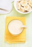 Batido de leche con el plátano en vidrio Imagenes de archivo