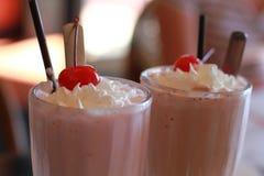 Batido de leche con la cereza y la crema Fotografía de archivo