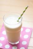 Batido de leche con la paja rayada en servilleta del lunar Fotos de archivo libres de regalías