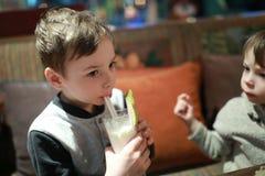 Batido de leche de consumición del niño Fotografía de archivo
