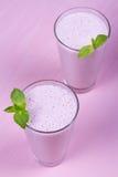 Batido de leche de las frambuesas adornado con la menta en fondo de madera rosado Fotografía de archivo libre de regalías