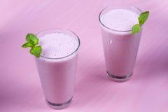 Batido de leche de las frambuesas adornado con la menta en fondo de madera rosado Imagen de archivo libre de regalías