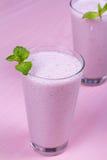 Batido de leche de las frambuesas adornado con la menta en fondo de madera rosado Foto de archivo