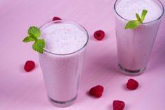 Batido de leche de las frambuesas adornado con la menta en fondo de madera rosado Imágenes de archivo libres de regalías