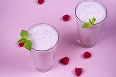 Batido de leche de las frambuesas adornado con la menta en fondo de madera rosado Imagen de archivo