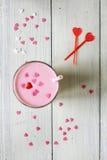 Batido de leche rosado asperjado con los corazones foto de archivo libre de regalías