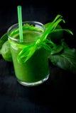 Batido e ingredientes verdes para ele no fundo de madeira preto Dieta detox Bebida saudável Foto de Stock