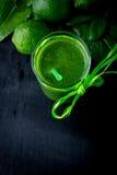 Batido e ingredientes verdes para ele no fundo de madeira preto Dieta detox Bebida saudável Vista superior Imagem de Stock
