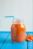 Batido saudável da cenoura em um frasco no fundo de madeira azul Imagem de Stock