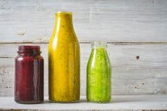 Batido verde, amarelo e vermelho na garrafa de vidro no fundo de madeira branco Imagem de Stock Royalty Free