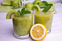 Batido verde com hortelã e frutos no fundo de madeira Foto de Stock