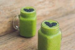 Batido verde fresco com banana e espinafres com coração do sesam foto de stock