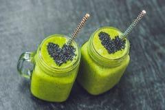 Batido verde fresco com banana e espinafres com coração de sementes de sésamo Amor para um conceito cru saudável do alimento Imagens de Stock Royalty Free