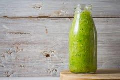Batido verde na garrafa de vidro no fundo de madeira branco Imagens de Stock Royalty Free