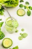 Batido verde no frasco com colher e vegetais Foto de Stock