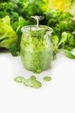 Batido verde no frasco e na colher de vidro no fundo branco Foto de Stock