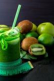 Batido verde perto do centímetro e ingredientes para ele no fundo de madeira preto Dieta detox Bebida saudável Imagens de Stock Royalty Free