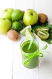 Batido verde perto dos ingredientes para ele no fundo de madeira branco Apple, cal, espinafre detox Bebida saudável Imagem de Stock