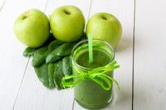 Batido verde perto dos ingredientes para ele no fundo de madeira branco Apple, cal, espinafre detox Bebida saudável Foto de Stock Royalty Free
