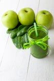 Batido verde perto dos ingredientes para ele no fundo de madeira branco Apple, cal, espinafre detox Bebida saudável Fotos de Stock Royalty Free