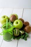 Batido verde perto dos ingredientes para ele no fundo de madeira branco Apple, cal, espinafre detox Bebida saudável Imagem de Stock Royalty Free