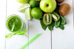 Batido verde perto dos ingredientes para ele no fundo de madeira branco Apple, cal, espinafre detox Bebida saudável Vista superio Imagem de Stock Royalty Free