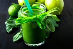 Batido verde perto dos ingredientes para ele no fundo de madeira preto Apple, cal, espinafre detox Bebida saudável Alimento claro Imagens de Stock Royalty Free