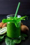 Batido verde perto dos ingredientes para ele no fundo de madeira preto Quivi e espinafres detox Bebida saudável Foto de Stock