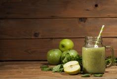 Batido verde recentemente misturado no frasco de vidro com palha Fundo de madeira Fotografia de Stock