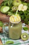 Batido verde recentemente misturado no frasco de vidro com palha Fundo de madeira Imagem de Stock