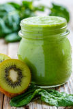 Batido verde saudável no frasco de ascendente próximo dos espinafres e do quivi Foto de Stock Royalty Free