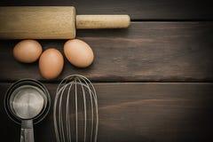 Batidor de huevo, huevos en la tabla de madera Fotografía de archivo