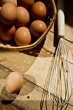 Batidor y cestas de huevos en fondo de madera foto de archivo