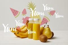 batidos amarelos da desintoxicação em umas garrafas com bananas, peras e quivis no fundo branco, yum yum yum inscrição fotos de stock